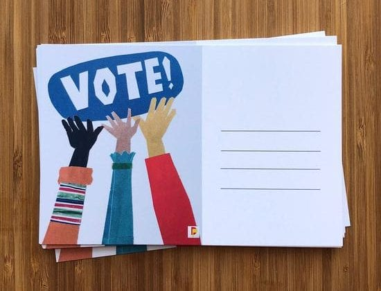 A stack of postcards with hands reaching towards the word VOTE
