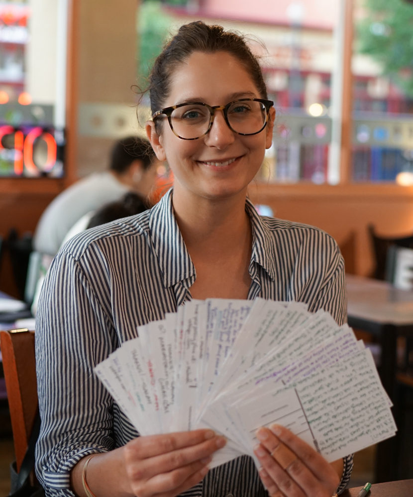 A female Washington DC volunteer holds a stack of postcard to voters
