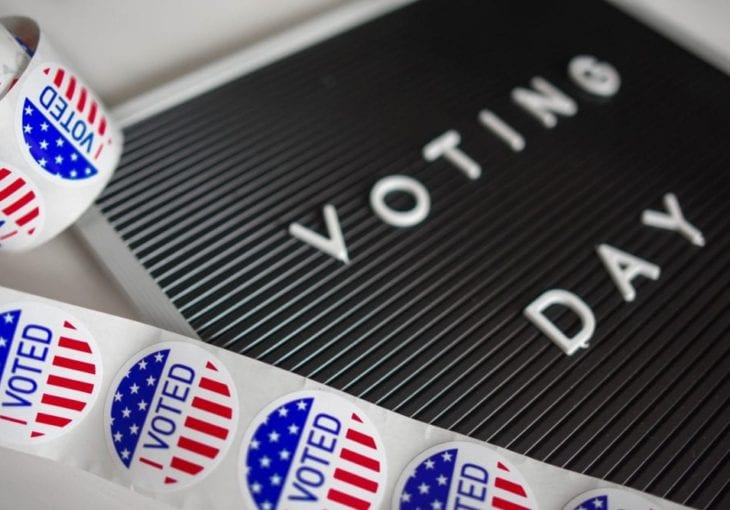 A board that reads Voting Day next to I voted stickers