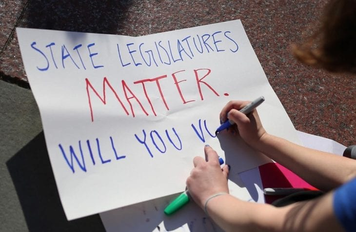 "A woman writes ""State legislatures matter. Will you vote?"" on a paper sign"