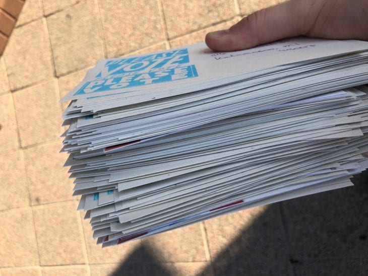 A stack of hundreds of handwritten postcards to voters being held in a person's hand