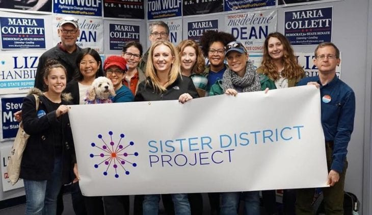 Volunteers from Washington, DC hold a Sister District sign