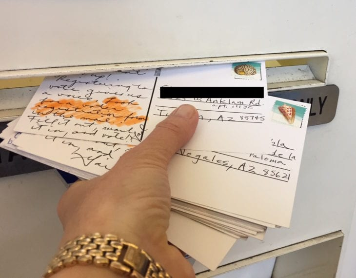A hand puts several dozen handwritten postcards to voters in a mail slot