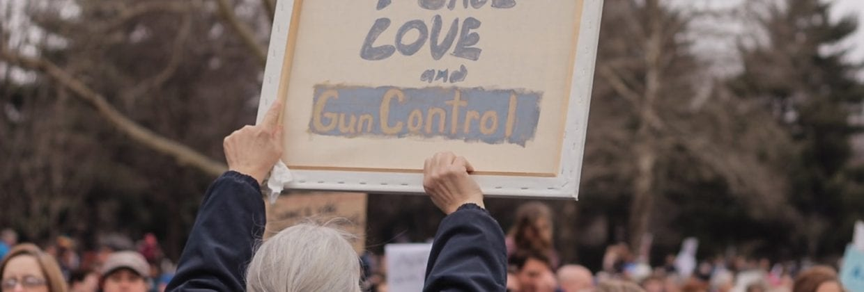 """Protester holds sign reading """"peace love gun control"""""""