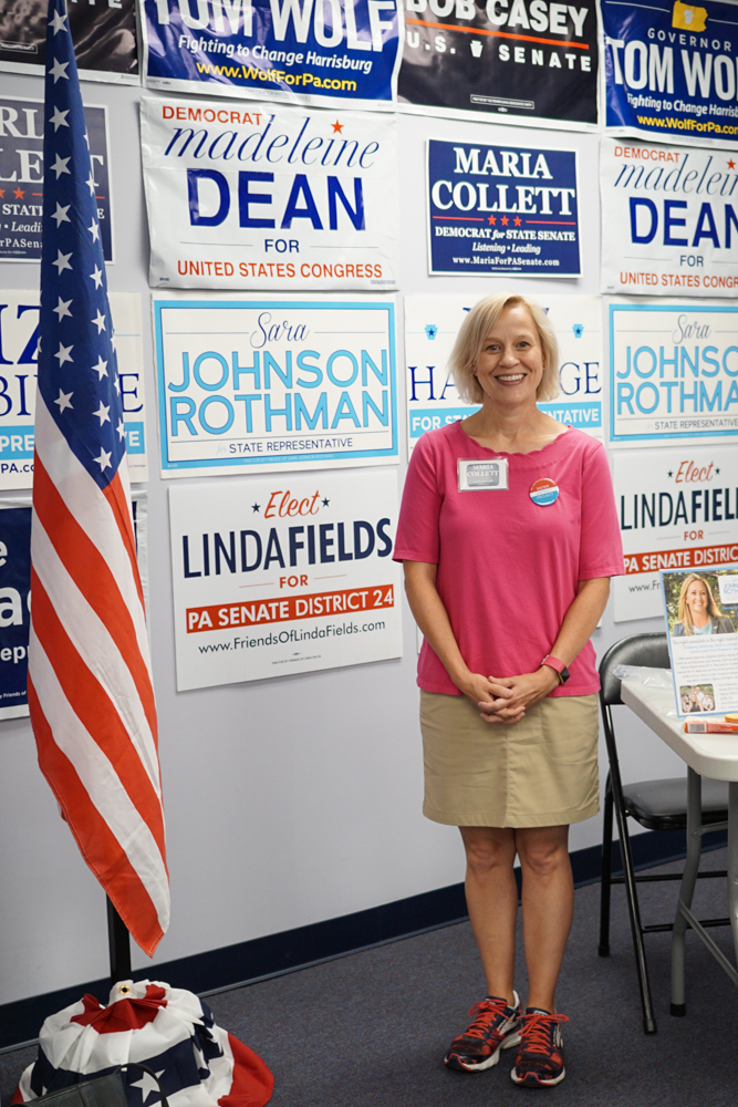 Sister District 2018 candidate Maria Collett poses with campaign signs at a canvass launch location in Pennsylvania.