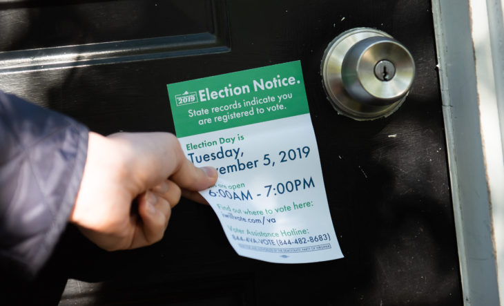 Hand placing Election Notice for November 5 on door