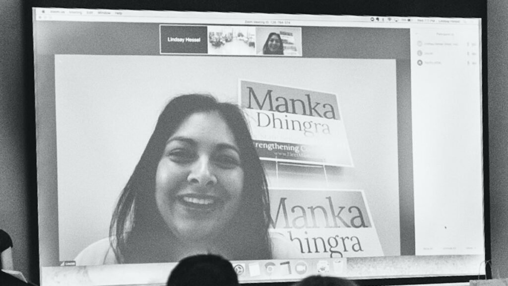 Black and white projector screen displaying a videoconference with a candidate